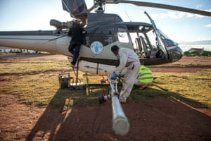 Men prepare a helicopter of the Food and Agriculture Organization of the United Nations (FAO), equipped with pesticide spreading equipment to fight a swarm of locusts, before taking off on May 7, 2014 in Tsiroanomandidy, Madagascar. FAO mission is to fight the locust's swarm with an insecticide.