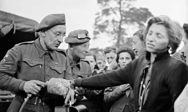 A British soldier sprays DDT (to combat insect-born typhus) on a recently liberated female prisoner from the Bergen-Belsen concentration camp