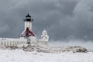St Joseph's Lighthouse above a frozen lake in South Haven, Michigan. Ice engulfs a red lighthouse as a fierce winter storm grips South Haven