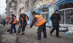 Street cleaners shovel debris from the scene of a mortar strike on city bus.