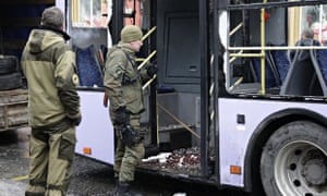 Pro-Russian rebels inspect the damaged bus in Donetsk