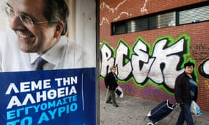 People walk past an election poster of Greek prime minister Antonis Samaras in Athens.