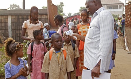 A health care worker, right,  takes the temperatures of school children for signs of the Ebola virus before they enter their school in the city of Conakry, Guinea, last Monday. Schools shuttered during the height of the Ebola crisis in Guinea began reopening Monday, but many parents were still too afraid to send their children to classes.