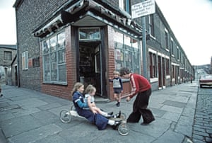 Children playing on a home-made go-cart outside a corner shop in Manchester, 1977
