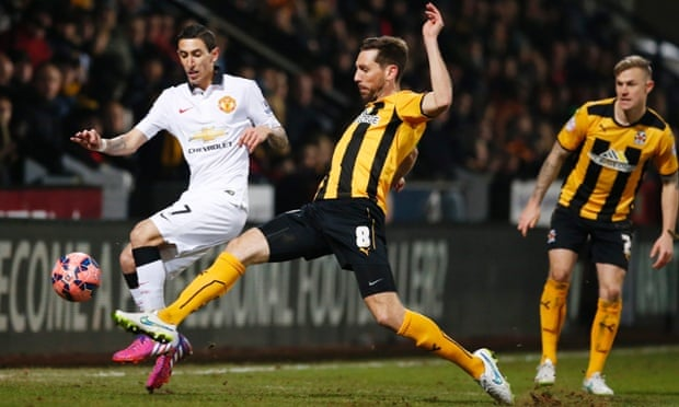 Cambridge United's Tom Champion challenges Angel Di Maria.