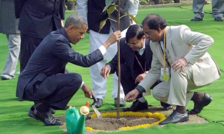 The US president plants a sapling after placing a wreath at the Mahatma Gandhi memorial.