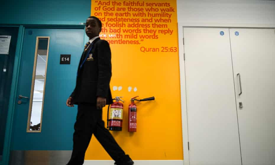 A pupil walks past an excerpt from the Qur'an, with more daubed on walls throughout the school.