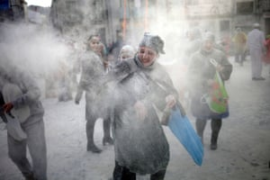 Clouds of flour hang in the air as people target each other in the festive battle.