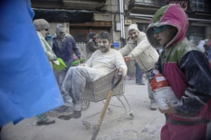 People sling flour at each other, with one shopping trolley-bound man using a shovel to gather the white powder.