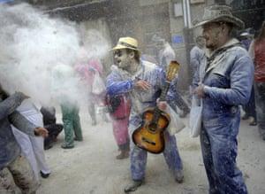 A man throws flour at another during the Domingo Fareleiro (floury Sunday in Galician language) festival in Xinzo de Limia.