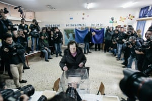 A woman casts her ballot at a polling station in front of a horde of journalists in a school in a suburb of Athens.