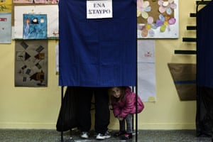 Peek-a-boo: a girl looks out from beneath the curtain of a voting booth at a polling station.