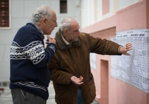 Voters check for names at a polling station in a school in Athens.