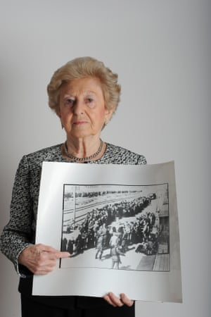 Irene Fogel Weiss holds a photo of her that was taken at Auschwitz by two Nazi guards