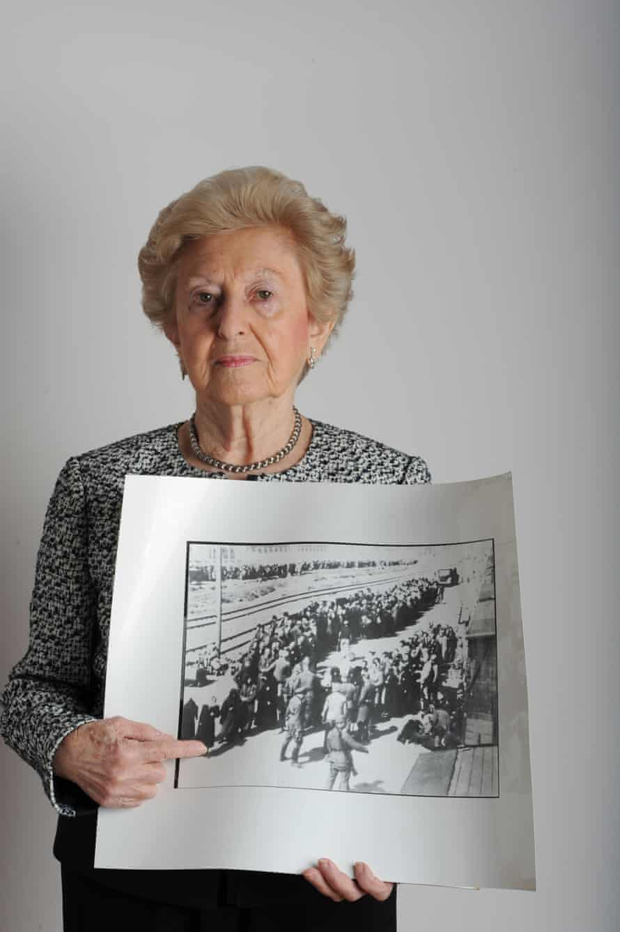 Irene Fogel Weiss holds a photo of her that was taken at Auschwitz by two Nazi guards.