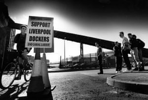 This photograph shows a group of sacked Mersey dockers picketing as management tries to recruit replacement workforce, 1995. At the time sacked Mersey dockers who had been dismissed weeks earlier after refusing to cross a picket line were picketing as their former employer, the Mersey Docks and Harbour Company continued to recruit a new workforce. The dispute became one of the longest in British Industrial history and lasted until February 1998 when striking dockers accepted a settlement.