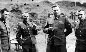 DrJosef Mengele, left, with Rudolf Hoss, Commandant of Auschwitz, Josef Kramer, Commandant of Belsen and a German officer.