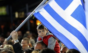 A child sitting on his father's shoulders attends a campaign rally by opposition leader and head of radical leftist Syriza party Alexis Tsipras.