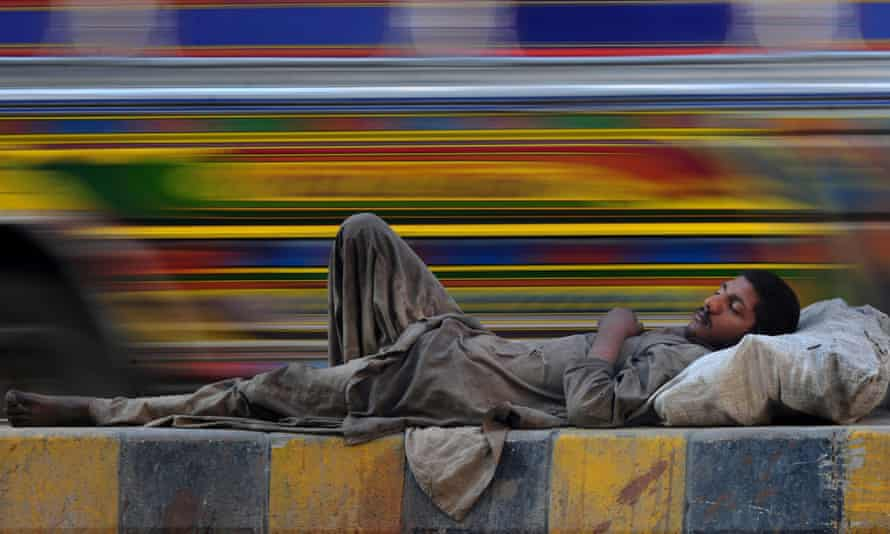 A Pakistani homeless man rests by a road in Karachi.