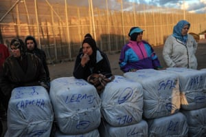 Women wait with their packages at the border crossing.