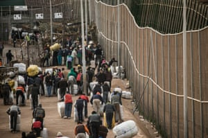 People wait at the border crossing. An increasing number of unemployed Moroccan men have started carrying bales as well, forcing some of the women out of work.