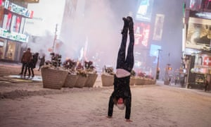 Jamina Goop, from Liechtenstein, does a handstand during a snow storm in Times Square, New York early on Tuesday.