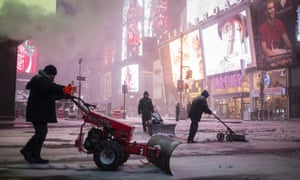 Workers clear the sidewalks during a snowstorm in Times Square, New York on Tuesday morning.