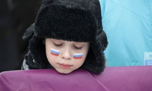 A young spectator has the Russian flag painted on the cheeks at the 2014 Sochi Olympic Games