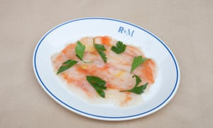 Pink seabass carpaccio with green sprigs on a plate