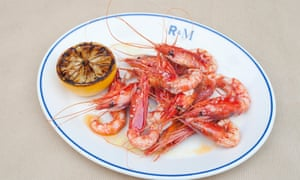Grilled red prawns in their shells with a grilled half lemon by the side