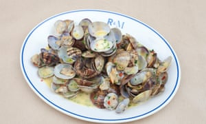 A pile of clams in their shells in a buttery sauce on a plate