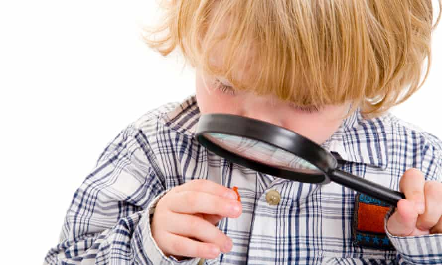 Boy looking at object through a magnifying glass