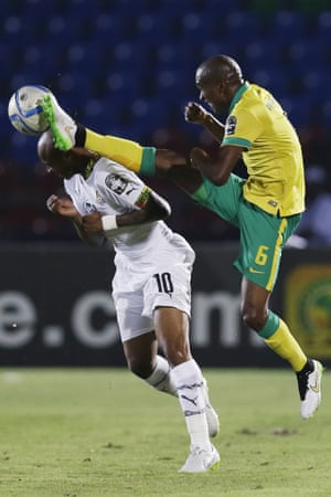 Ghana's Andre Ayew, left, bravely goes in for a challenge with the flying boot of South Africa's Anele Ngcongca,