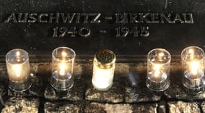 Candles burn by a memorial plaque at the Birkenau Nazi death camp in Poland.