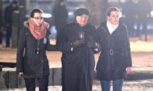 Auschwitz survivor Roman Kent (C) lights candle in Auschwitz