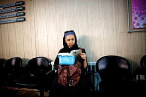 A woman reads a book as she waits for chemotherapy at a clinic in Tehran, Iran