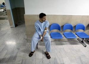 An Iranian man sits in a corridor at Loqman hospital in Tehran