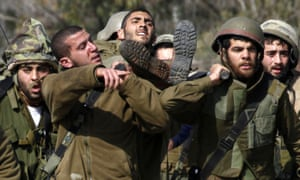 An injured Israeli soldier is carried from the scene after an anti-tank missile hit an army vehicle