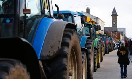 A woman walks down a line of tractors during an anti-fracking protest in Preston, northern England January 28, 2015. A local English government council has voted to delay a decision on whether shale gas firm Cuadrilla can progress with two fracking projects, in a case that is being closely watched by the industry and environmental campaigners.