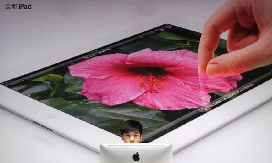 An employee sits in front of a poster advertising the New iPad at an Apple dealership in Wuhan, Hubei province, China.