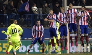Lionel Messi curls a free-kick over the wall but the Atletico keeper Jan Oblak is more than equal to it.