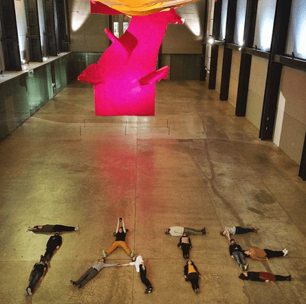participants at the #emptytate event lie on the floor of the Tate Modern's Turbine hall spell out the word T-A-T-E