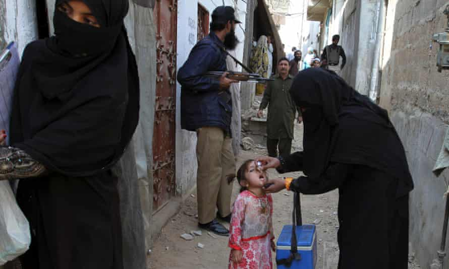 A health worker in Karachi vaccinates a girl against polio while an armed guard provides security.