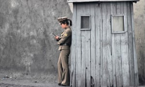 A North Korean soldier uses her mobile phone next to a sentry on the banks of the Yalu River, near the North Korean town of Sinuiju, opposite the Chinese border city of Dandong.