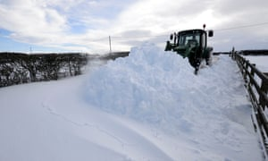 A farmer uses a tractor to clear a road of snow in Oakenshaw, County Durham.