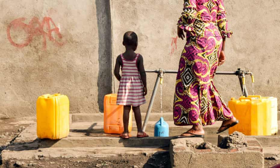 A woman and her child fill on June 16, 2014 containers at a water pump belonging to the public water distribution service Regideso in the center of the northeastern city of Goma, where most of the one million residents of the city are still waiting to have clean, uncontaminated running tap water in their homes.