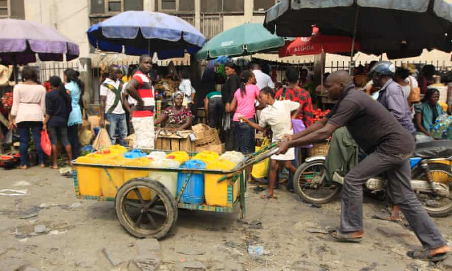 A man push cart with water at a market in Obalende  Lagos, Nigeria, Saturday, Jan. 14, 2012.  Nigeria's government will meet with labor unions in a last bid to halt a paralyzing national strike that now threatens oil production in Africa's most populous nation.