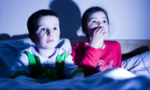 siblings watching TV in bed together