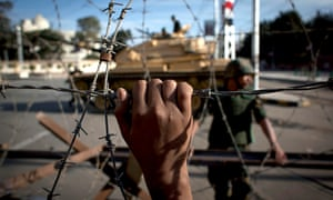 An Egyptian army tank is seen behind barbed wire.