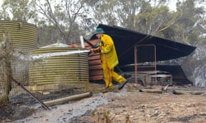 A Country Fire Service volunteer douses spot fires beside a burnt out shed near One Tree Hill in the Adelaide Hills.